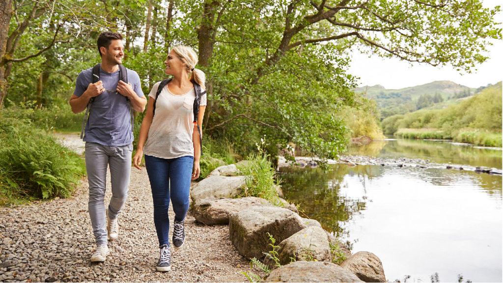 Två personer som promenerar i skogen och pratar.