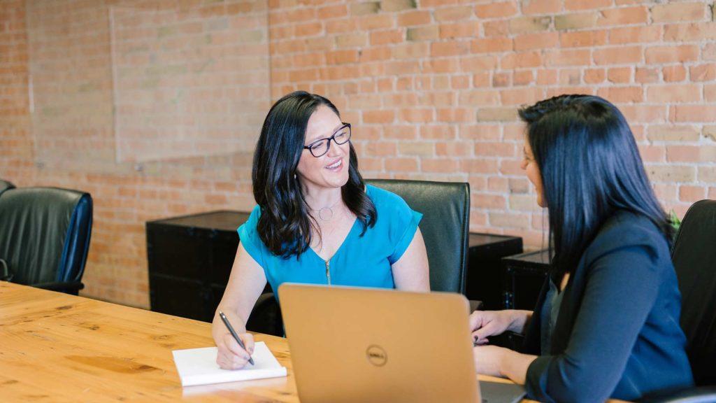 Två unga kvinnor sitter och pratar med dator och anteckningsblock framför sig.