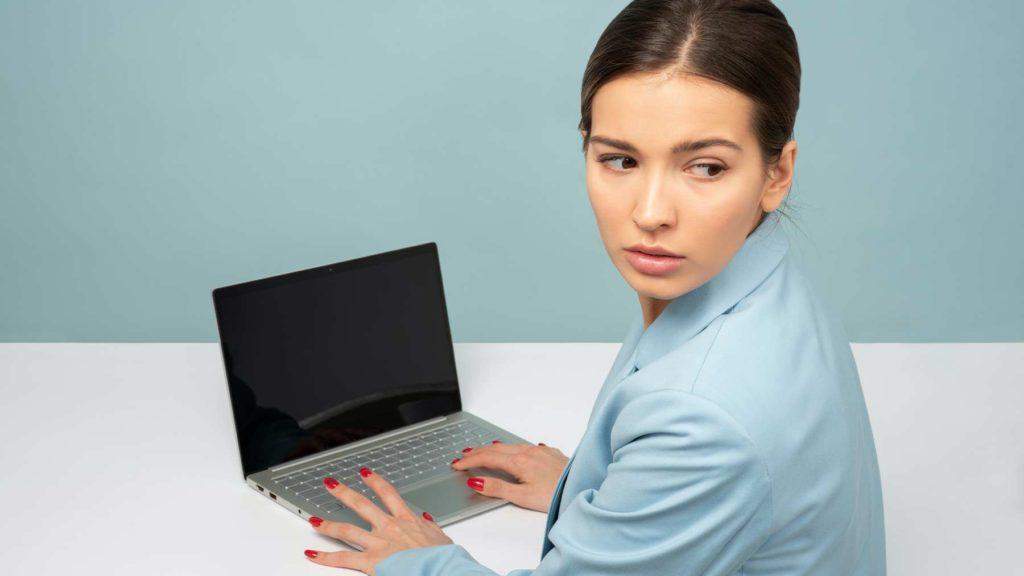 En kvinna som sitter vid en dator tittar bakåt och ser orolig ut.