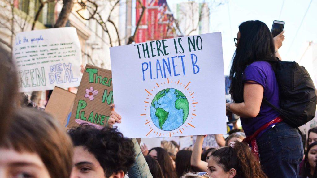 En demonstration med många ungdomar. En person håller upp en skylt med texten