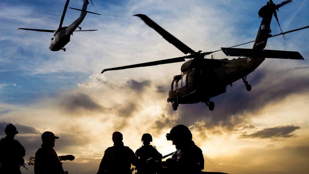 En militär operation med soldater och helikoptrar i luften i skymningen.