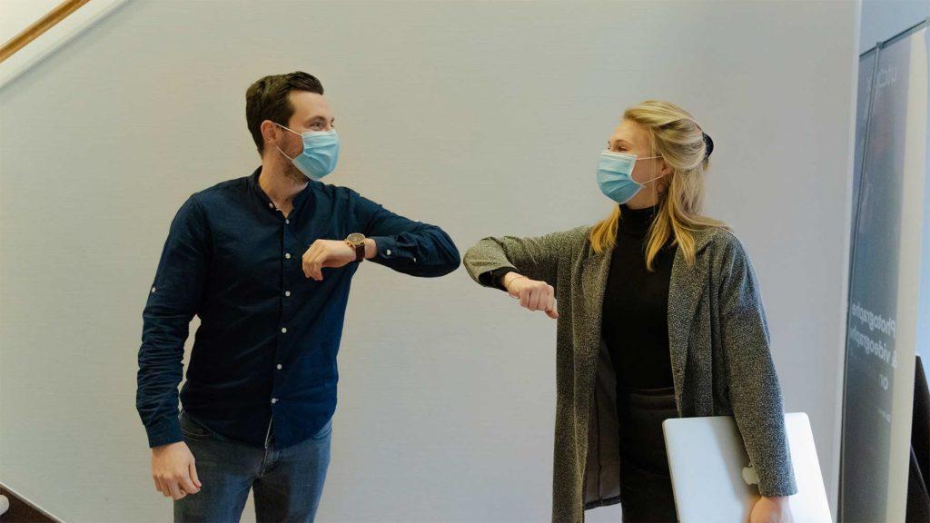 En ung man och kvinna, båda iförda munskydd,