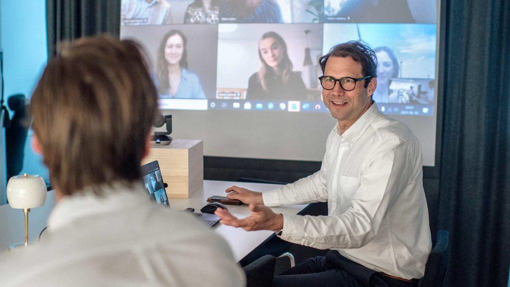 Johannes Hylander sitter vid ett skrivbord och samtalar med en medarbetare. Bakom honom syns en skärm där många medarbetare är uppkopplade för ett digitalt möte.
