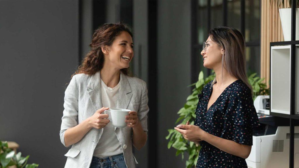 Två kvinnor på ett kontor pratar med varandra och ler.