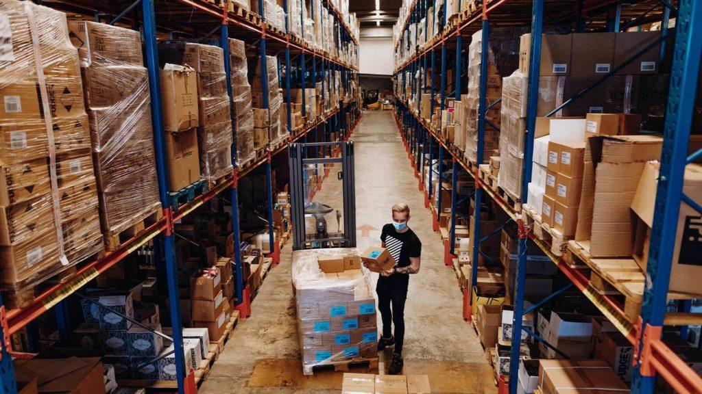 En ung kille med munskydd arbetar ensam i en stor lagerlokal.