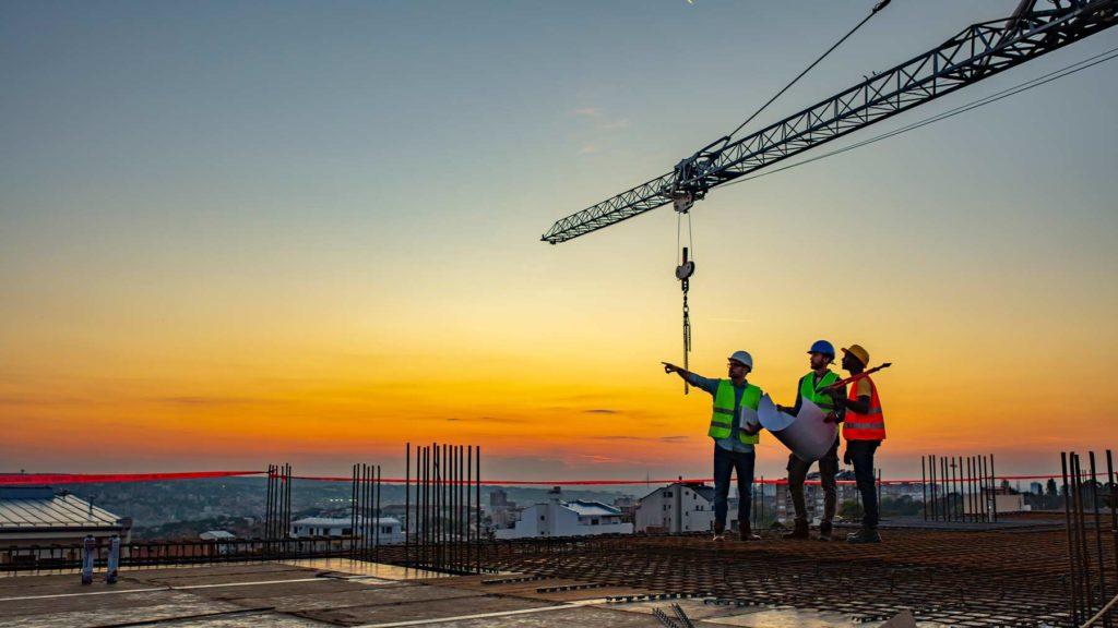 Tre män som arbetar på en byggarbetsplats står och pratar. Det är solnedgång.