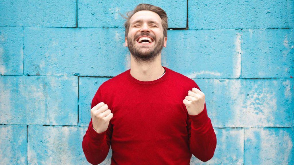 En ung man knyter nävarna i en segergest och ser euforisk ut. Bakom sig har han en blå tegelvägg.