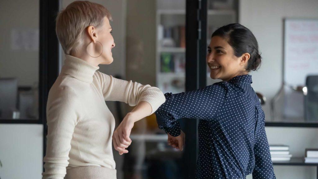 Två kvinnliga kolleger hälsar på varandra genom att stöta till varandra.med armbågarna.