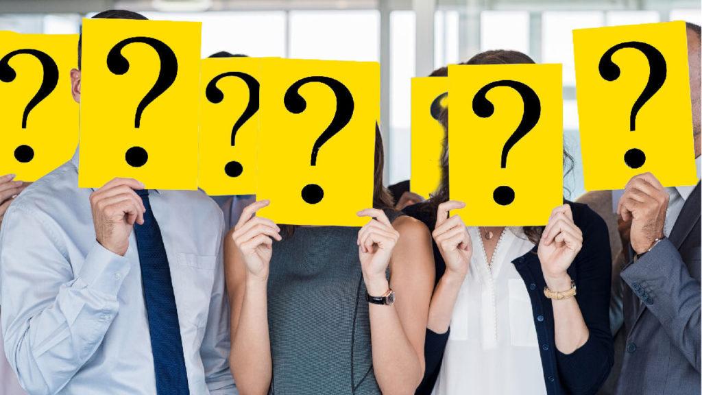 En grupp personer håller upp gula skyltar med frågetecken på framför sina ansikten.