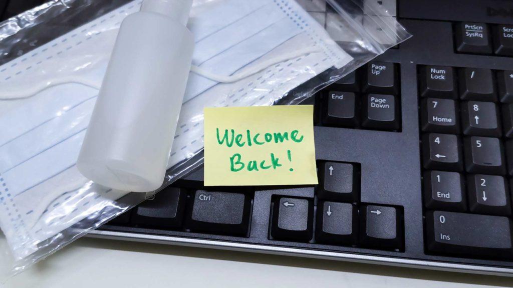 Ett tangentbord och ovanpå ligger ett munskydd och en liten flaska handsprit. Och en lapp med texten:
