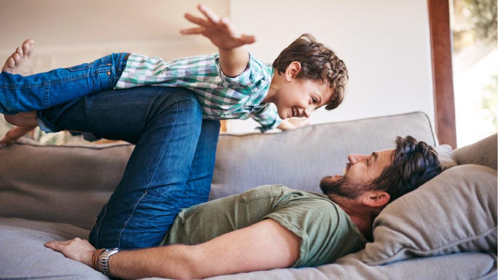 Glad man som leker med ett barn i en soffa.
