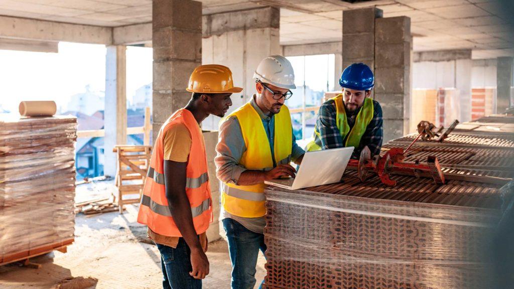 Tre män iförda arbetskläder står och diskuterar på en byggarbetsplats.