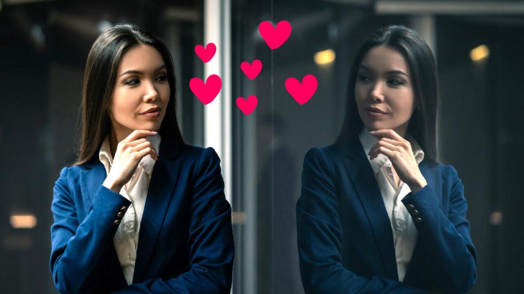 En kvinna med långt mörkt hår tittar sig i spegeln. Vid hennes ansikte finns rosa hjärtan.