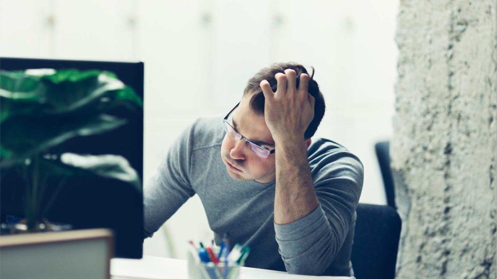 En bekymrad man sitter vid sitt skrivbord och lutar huvudet mot ena handen.
