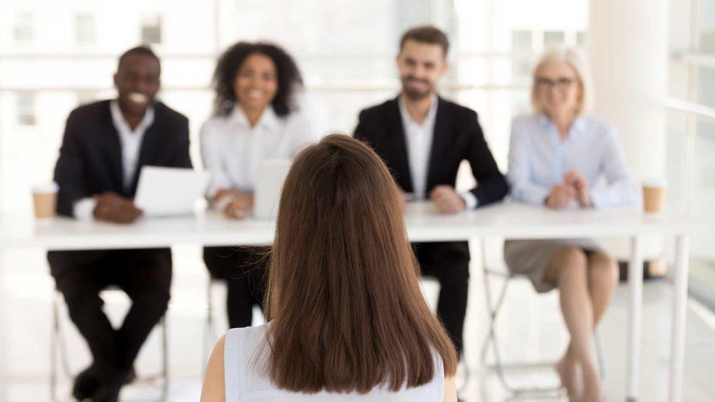 En mörkhårig kvinna sitter med ryggen mot fotografen. Hon blir intervjuad av fyra rekryterare som sitter mitt emot henne.