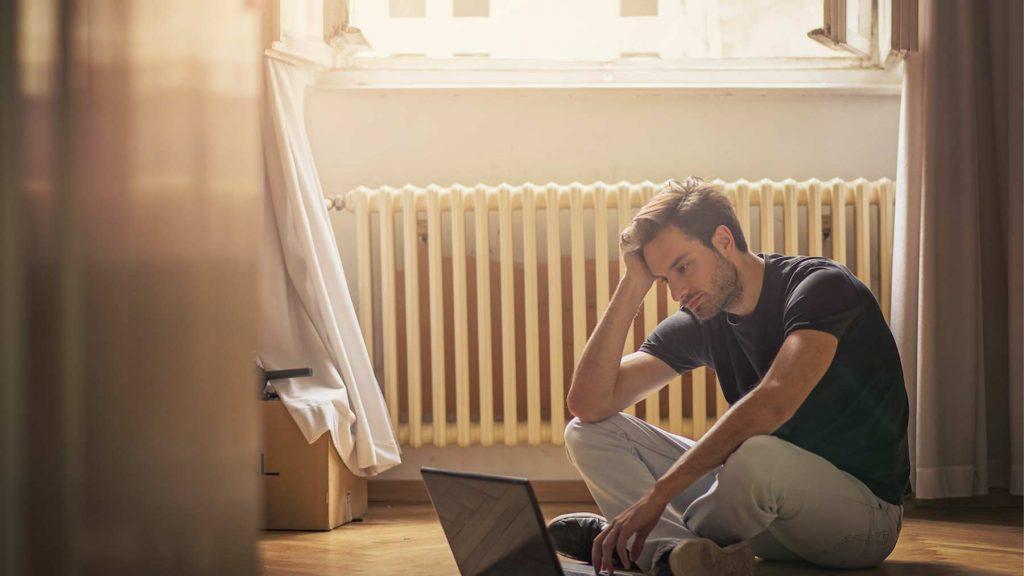 En ung man sitter framför en dator och ser bekymrad ut.