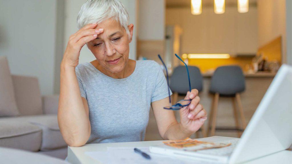 En äldre kvinna sitter vid ett skrivbord och stödjer sitt huvud mot ena handen.