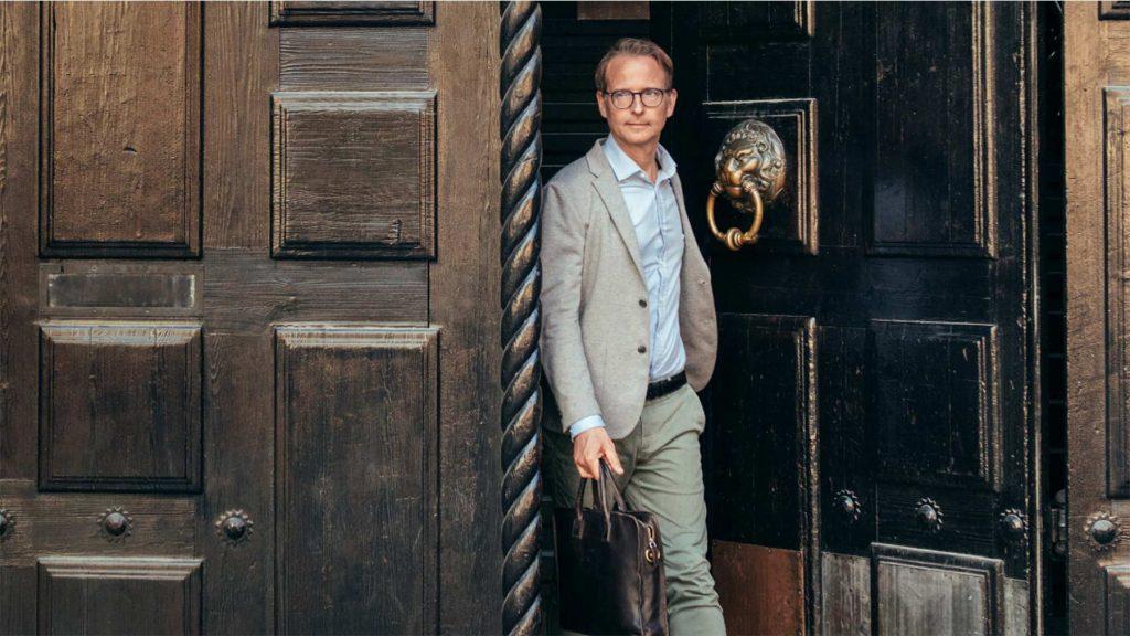 Lars Strannegård går ut genom Handelshögskolans massiva port.