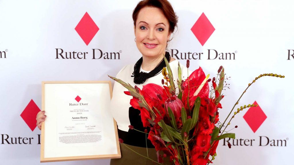 Anna Borg med blommor och diplom i famnen.