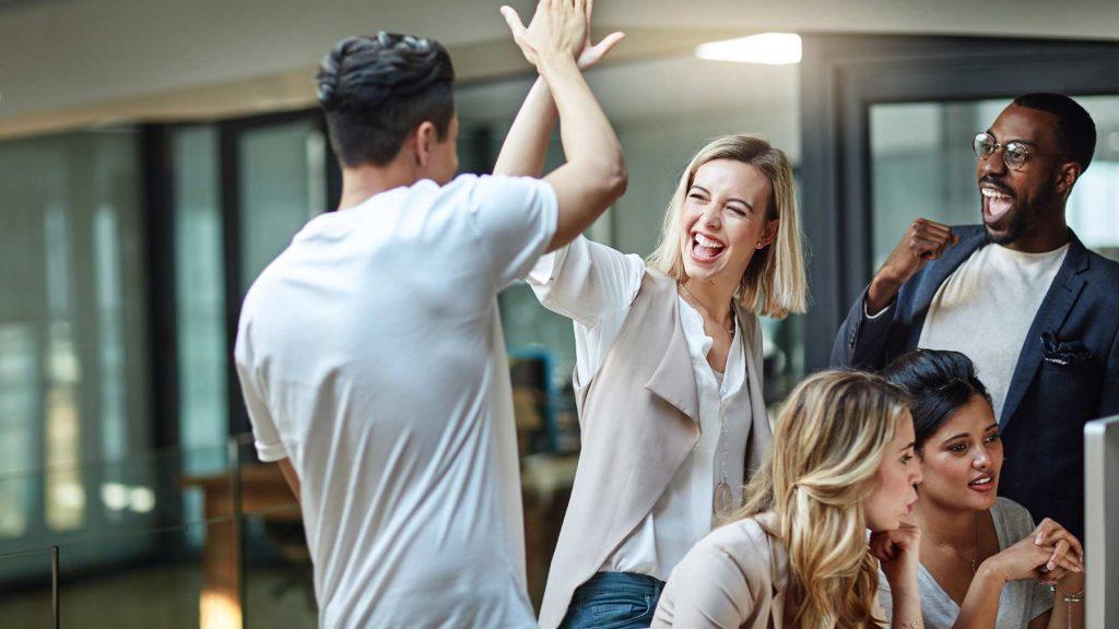 En man och en kvinna gör high five inför medarbetarna.