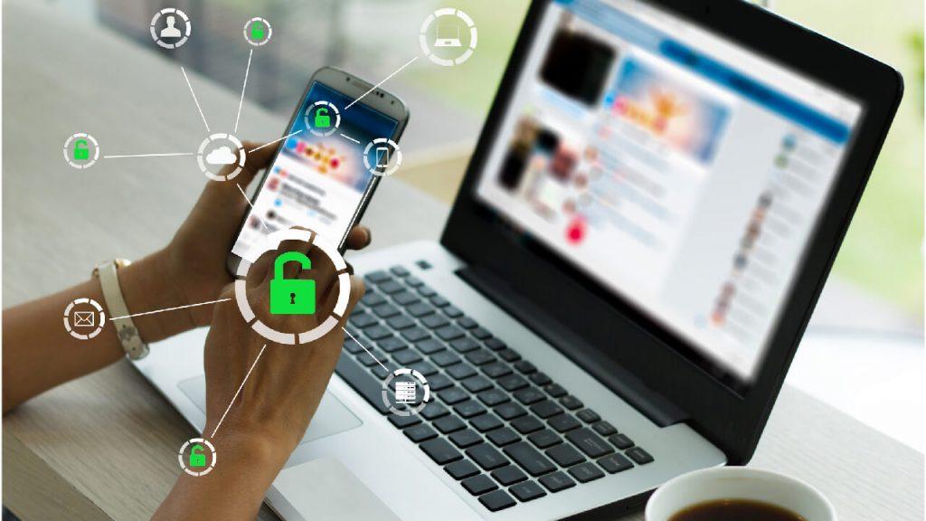 En dator med en kopp kaffe bredvid. Över den ser man ett par händer som jobbar med en telefon.