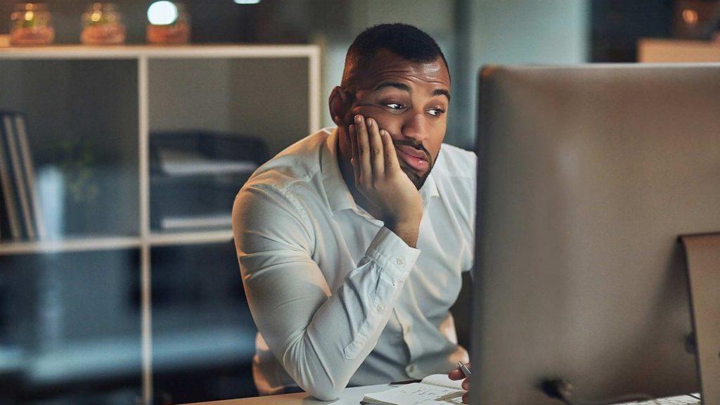 En man sitter framför en dator och ser uttråkad ut.