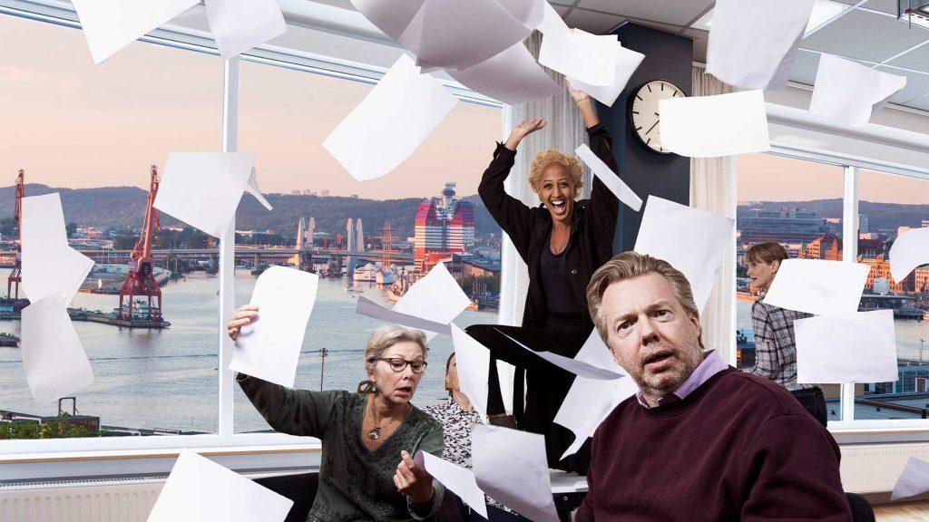 Några medarbetare kastar papper omkring sig på ett kontor med utsikt över vattnet.